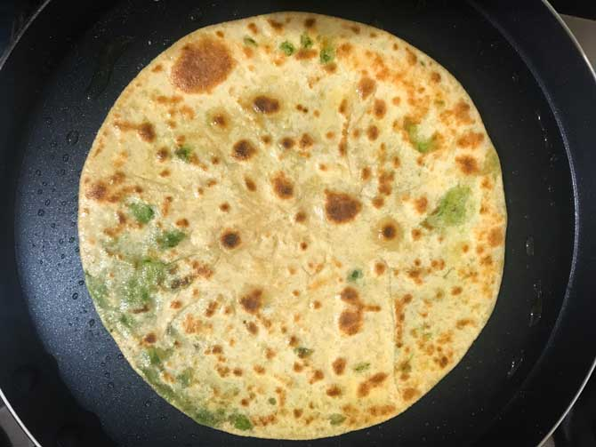 Ghee applied on matar paratha and cooked