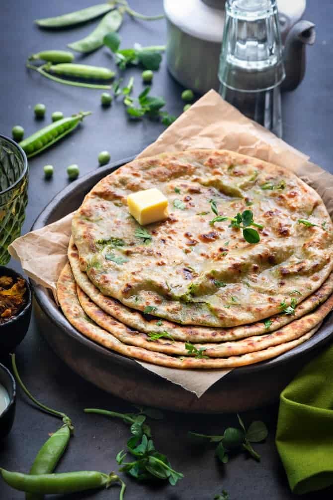 Stacked peas paratha or matar paratha topped with butter served on black plate. Teapot and cups at the back.