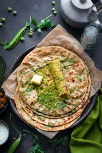 Overhead shot of spicy Matar paratha on black plate with top paratha cut open to show the peas filling.