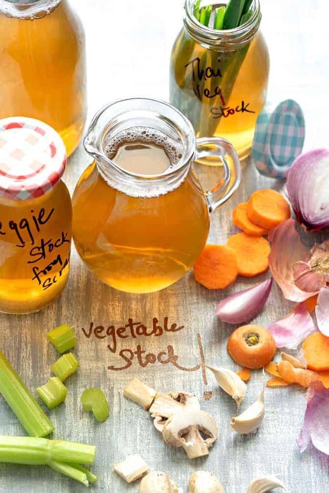 Vegetable Broth in glass pitcher and bottles along with some veggies spread around