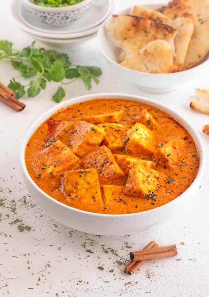 Paneer butter masala gravy in white bowl with naan bread at the back.