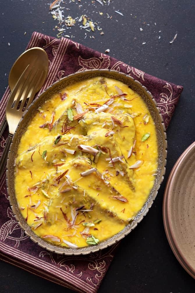 Overhead shot of Hyderabadi Shahi Tukda or Shahi Toast served in oval brass platter.