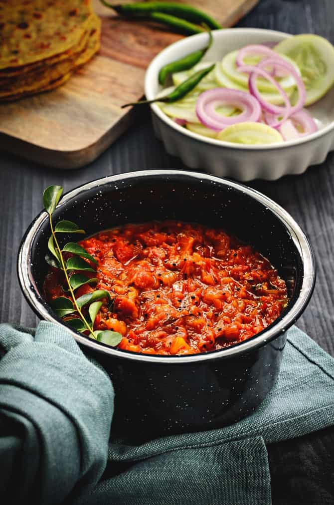 Andhra style tomato chutney recipe or Thakkali chutney in pan with salad at the back.