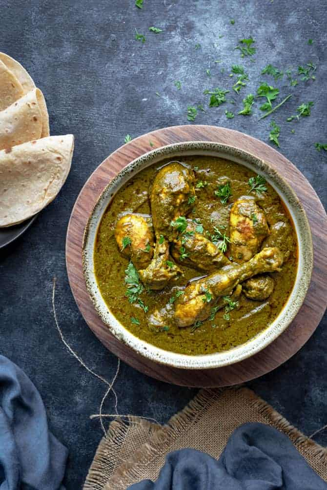 Chicken saag wala curry served in a bowl with Indian roti bread on the side.