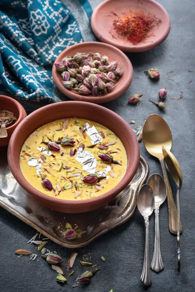 Garnished Rabdi served in an earthen pot, few rose buds and saffron at the back.