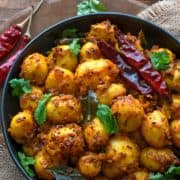 Close up shot of spicy roast baby potatoes served in black plate