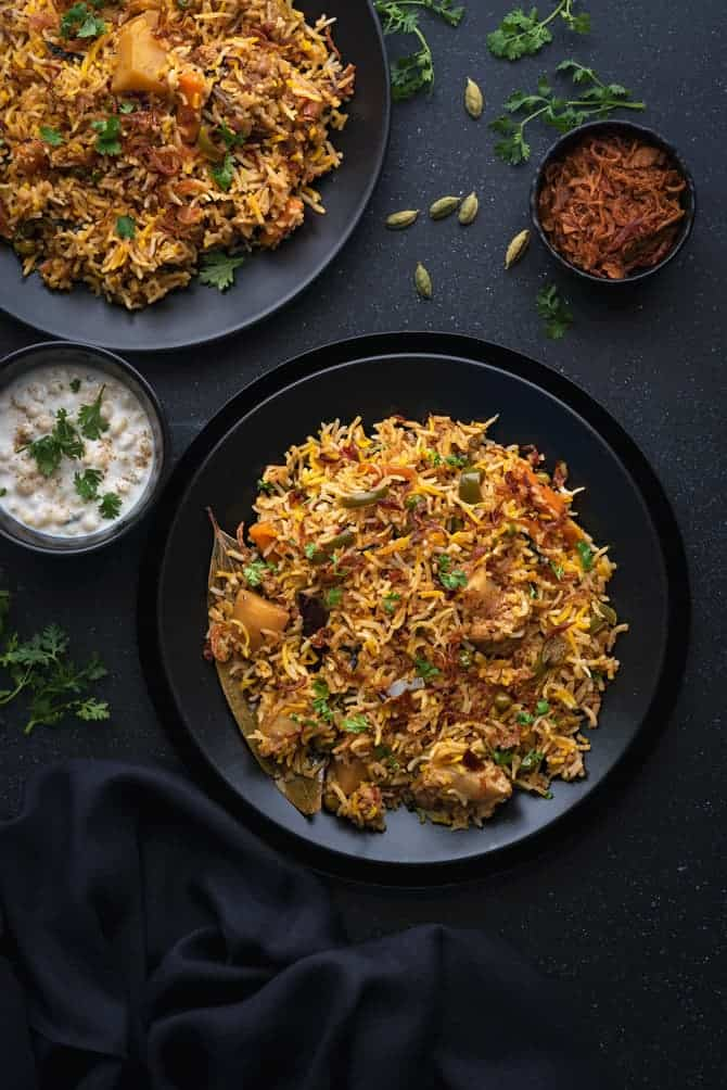 Instant pot vegetable biryani served in 2 black plates with Indian raita on side.