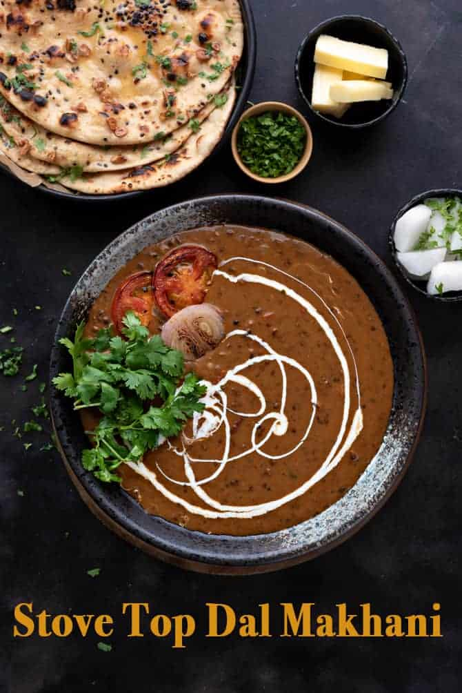 Overhead shot of dal makhani served in black bowl with naan bread and butter on side.