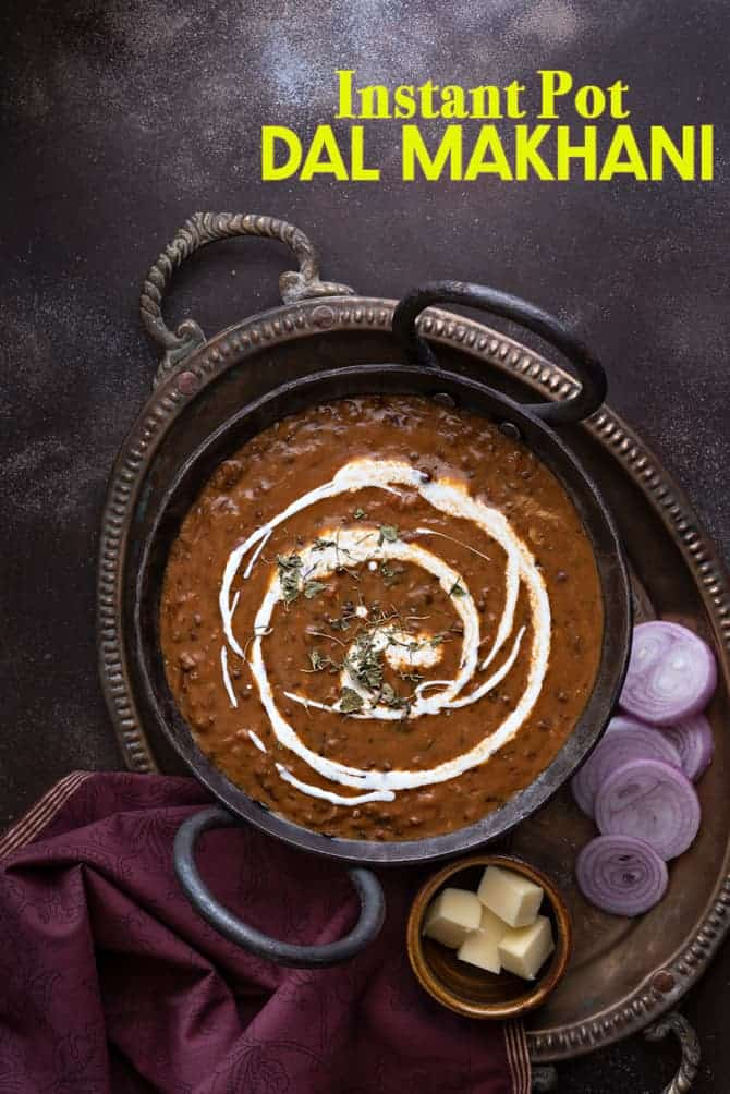 Overhead shot of dal makhani served in traditional kadhai with onion rings and butter on the side.