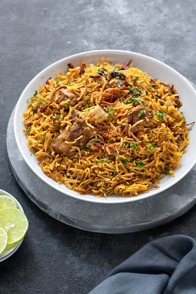 Instant pot Lamb Biryani served in white plate with lemon wedges on the side.