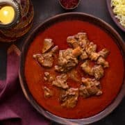 Traditional Awadhi Mutton Korma or lamb korma in wooden bowl with saffron rice on the side.