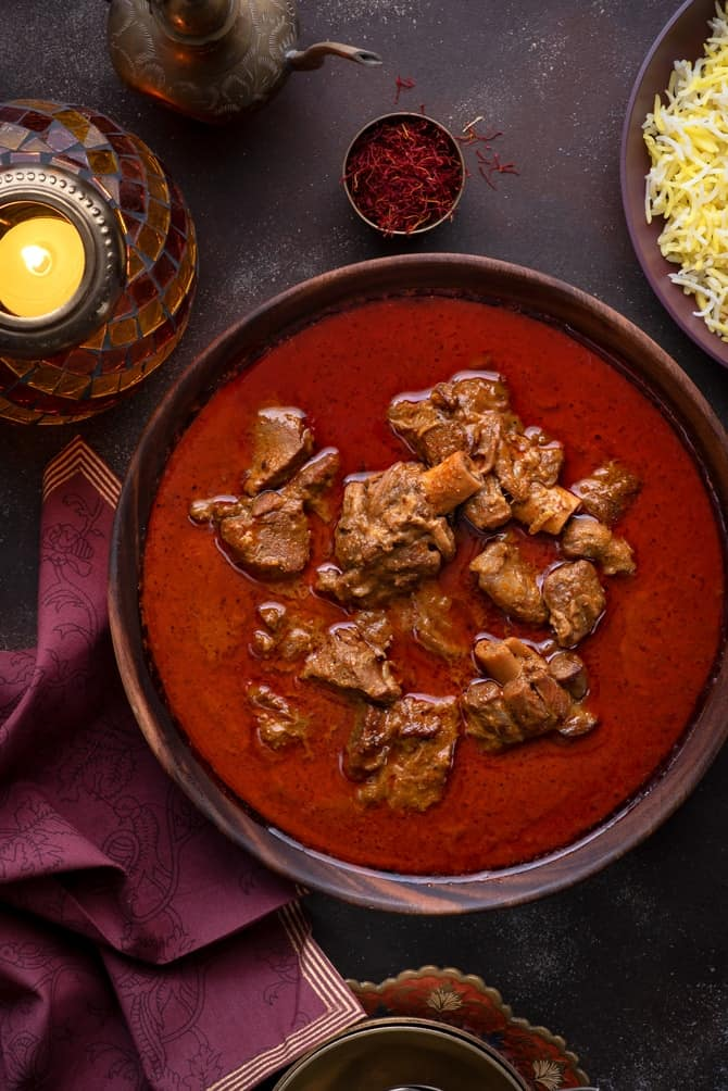 Traditional Awadhi Mutton Korma or lamb korma in wooden bowl with saffron rice on the side