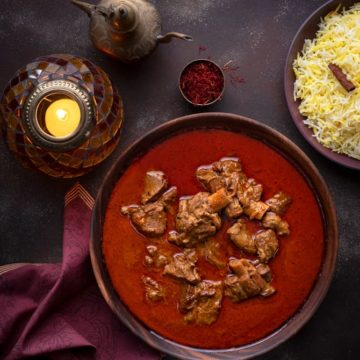 Overhead shot of Mutton Korma or Lamb Korma in wooden bowl with saffron rice on the side