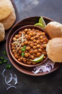 Chana Masala or chole served in wooden bowl along with puris, lemon wedges and onions on the side.