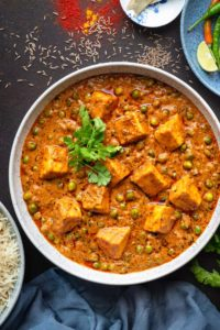 Close up shot of restaurant style matar paneer curry served in large white bowl.