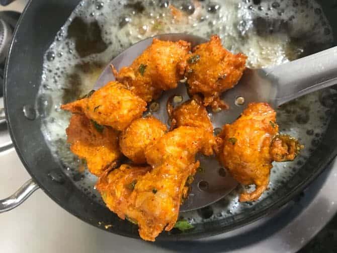 Crisp fried chicken pakora on ladle.