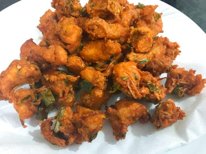 Fried chicken pakora on absorbent paper on plate, ready to serve.