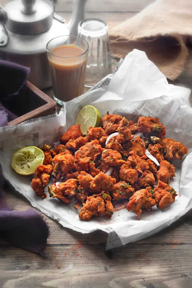 Crispy chicken pakora or chicken fritters on parchment lined paper, tea glass at the back.
