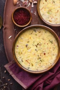 Sheer Korma in two brown bowls, saffron in a small bowl on wooden tray.