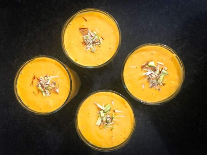 Mango lassi served in 4 glasses and garnished with saffron strands and slivered nuts.