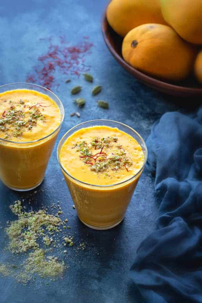 Mango Lassi served in two glasses, mangoes at the back, nuts, saffron and cardamom spread around.