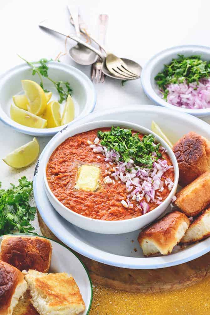 Garnished Pav Bhaji served in white bowl, with buttered pav, chopped onions, lemon wedges on the side.