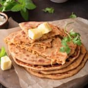 Close up shot of mooli ka paratha topped with butter, one paratha cut open to show the stuffing within.