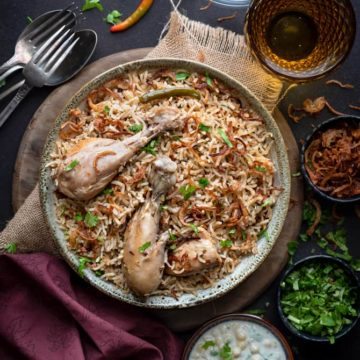 Spicy chicken pulao served in grey ceramic bowl, yogurt raita and fried onions on side.