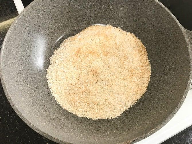 Dry roasting coconut powder in pan.