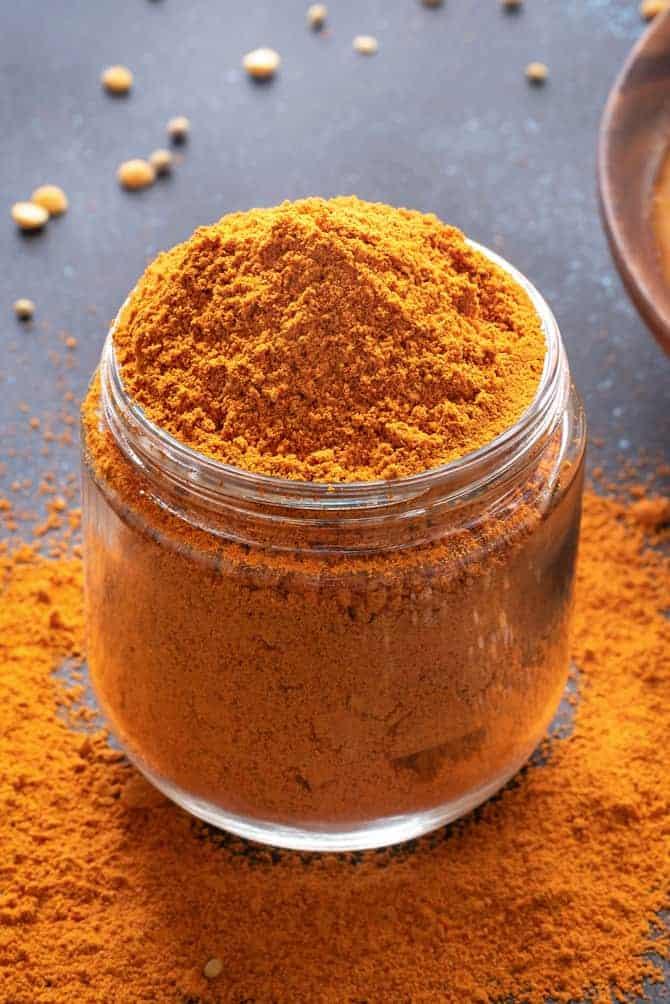 Close-up shot of homemade sambar powder or sambar masala in a glass jar.