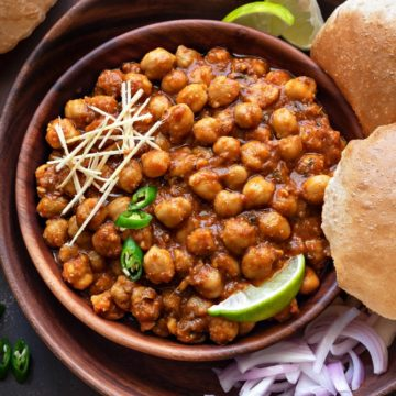 Close up shot of Chana Masala or chole in wooden bowl with puris, onions and lemon wedges.