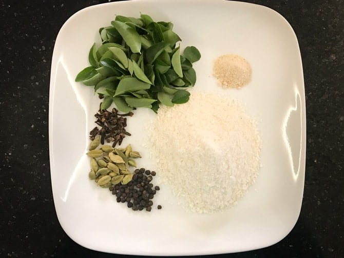Curry leaves, hing, cloves, black peppercorns, coconut powder, green cardamom on white plate.