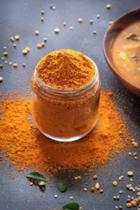 Sambar Masala powder in a glass jar, few curry leaves around, sambar in a bowl at the back.