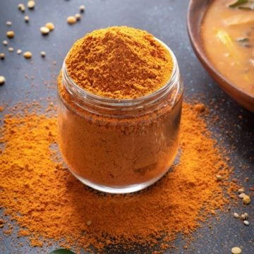 Sambar Masala powder in a glass jar, few curry leaves around, sambar in a bowl at the back.
