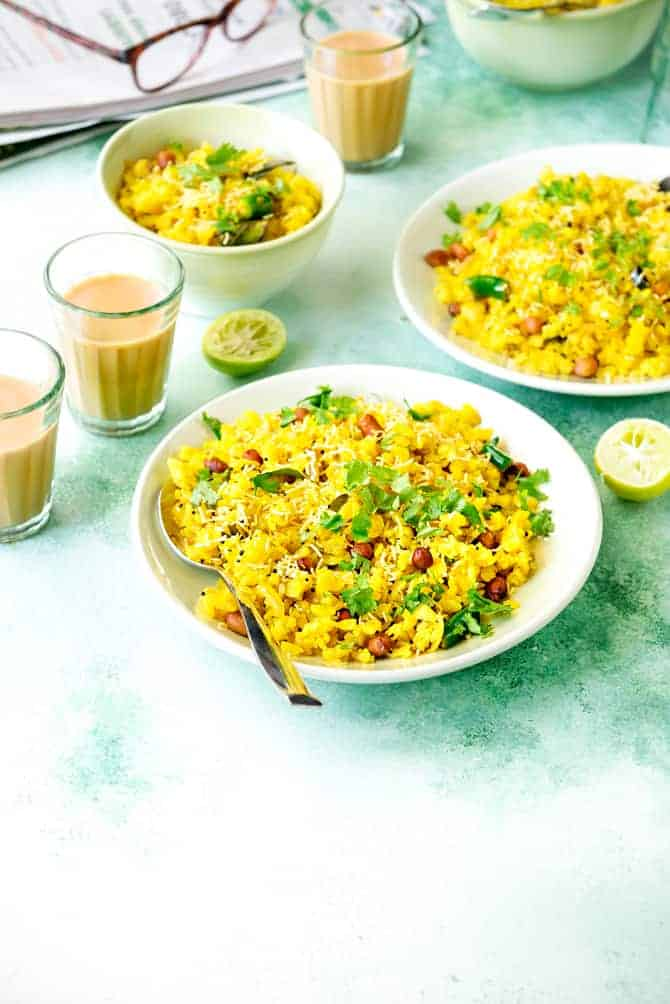 Kanda Poha on green ceramic plate with a spoon in it, tea in a glass at the back.