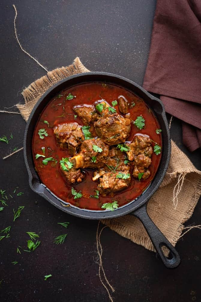 Overhead shot of Indian mutton curry or lamb curry in cast iron pan, some coriander leaves spread around.