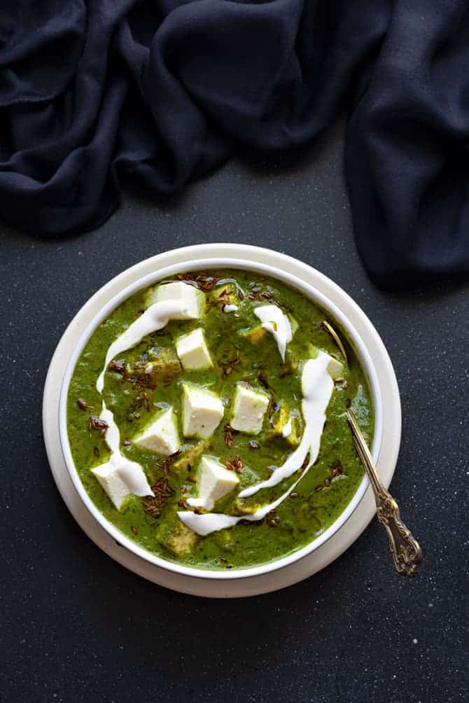 Instant Pot palak paneer in a white bowl, with a spoon into it.