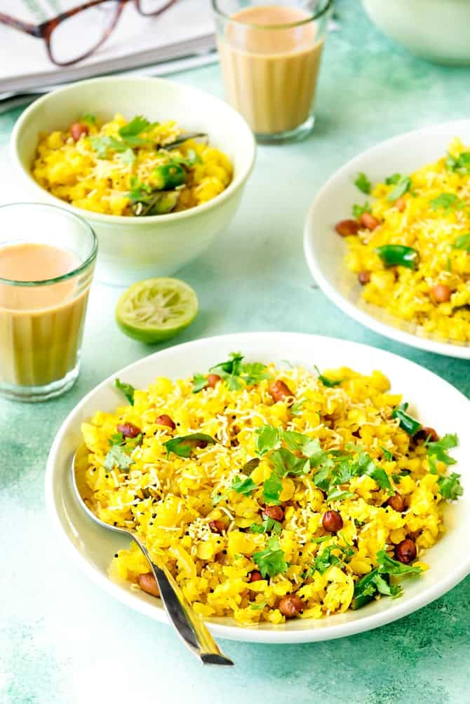 Close up shot of poha on a green plate and in bowl at the back, tea in glass on the side.