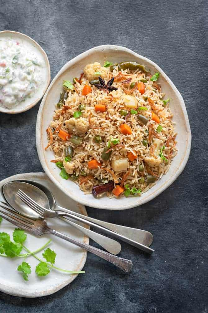 Vegetable pulao on white ceramic plate with raita and spoons on the side.