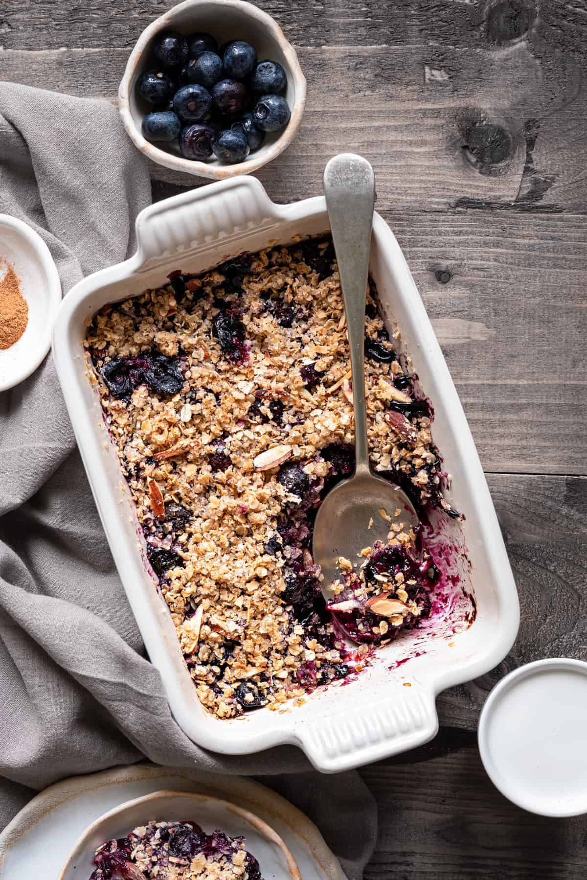 Blueberry crisp in rectangular ceramic dish with a spoon, cream and some blueberries on side.