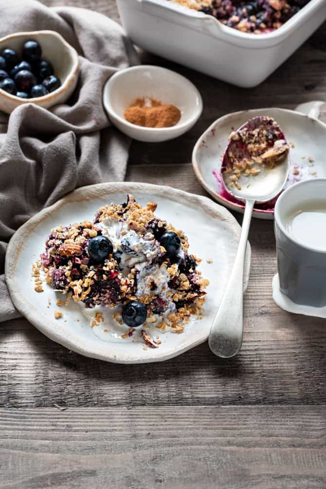 Cream topped blueberry crisp served on white plate with cinnamon powder, spoon and blueberries placed in background.