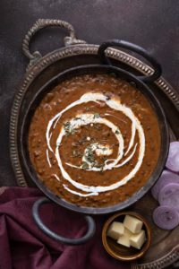 Close up shot of restaurant style Punjabi dal makhani or kali dal served in traditional kadhai.