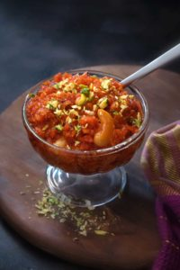 Close up shot of dry fruits garnished carrot halwa or gajar ka halwa sweet in a glass bowl.