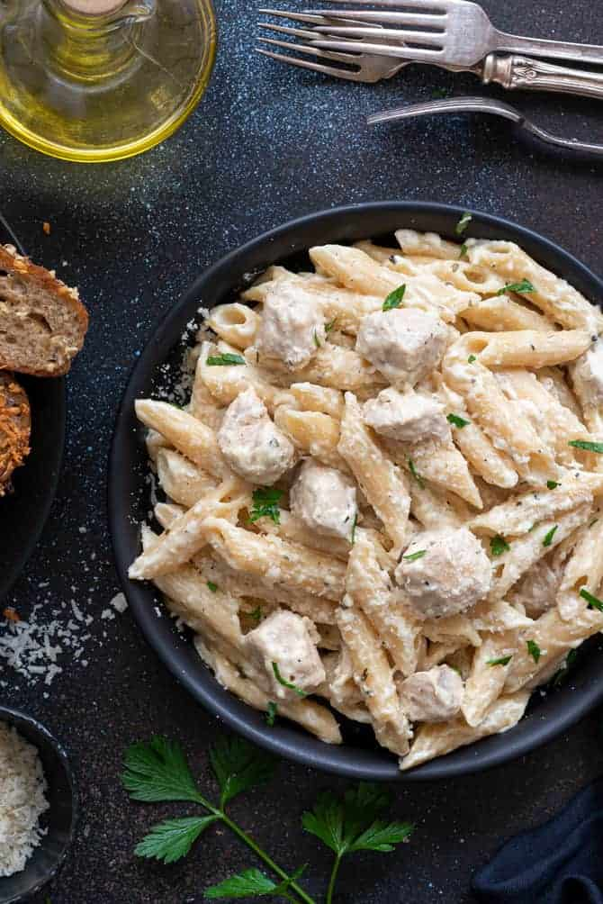 Close up shot of chicken Alfredo pasta served in a black plate.