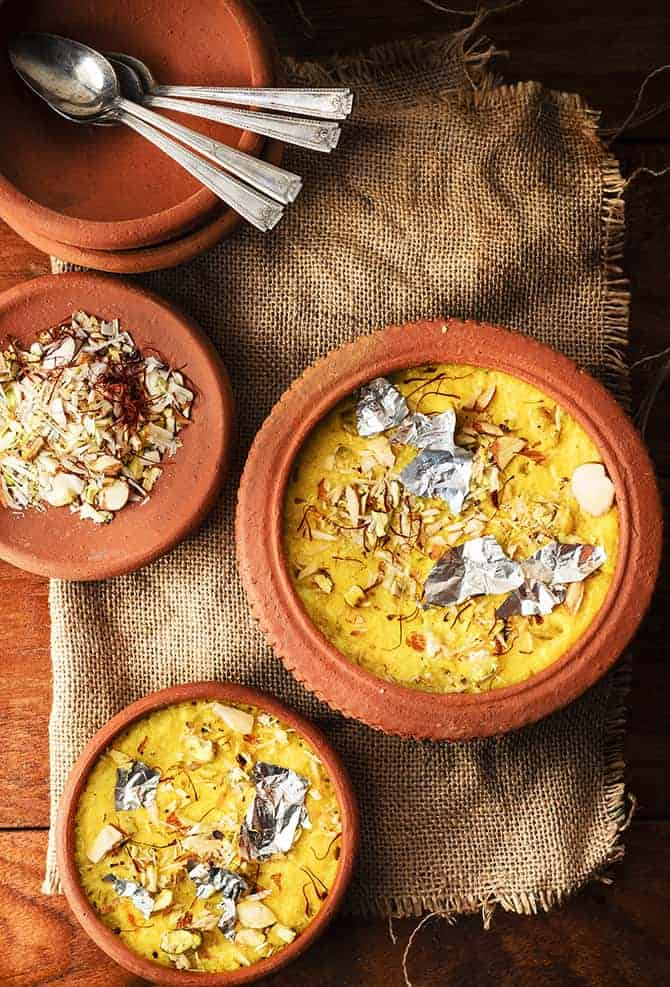 Overhead shot of kesar phirni sweet in two earthen pots, chopped dry fruits and spoon on side.