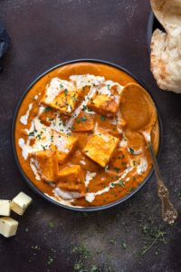 Close up shot of paneer butter masala served in a black plate with a spoon.
