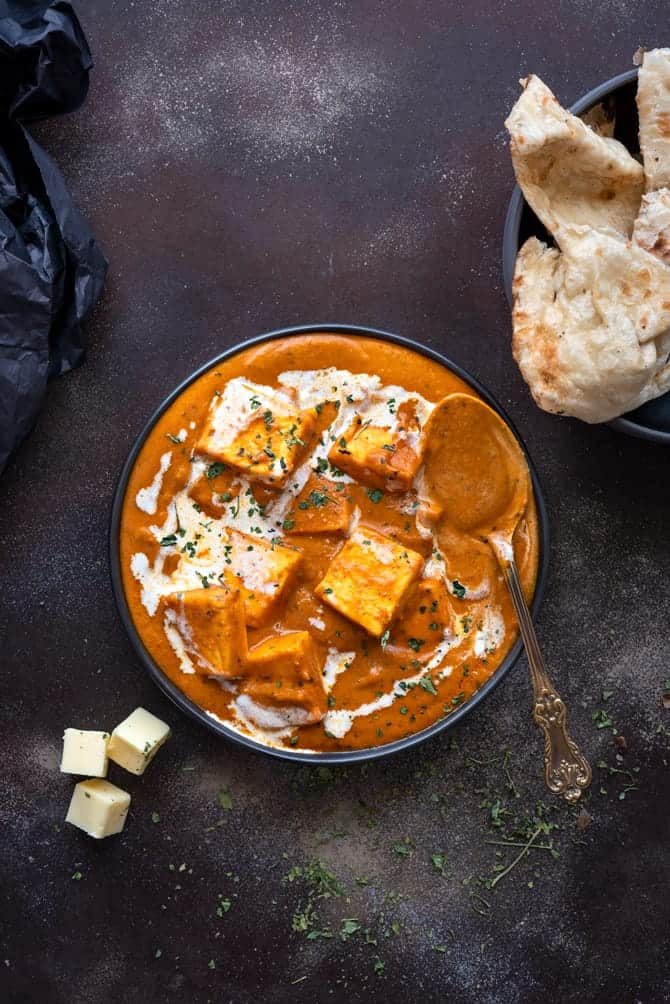 Overhead shot of paneer butter masala served in black plate with some naan bread on the side.