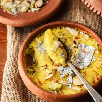 Close up shot of kesar phirni sweet in earthen pot with a spoon.