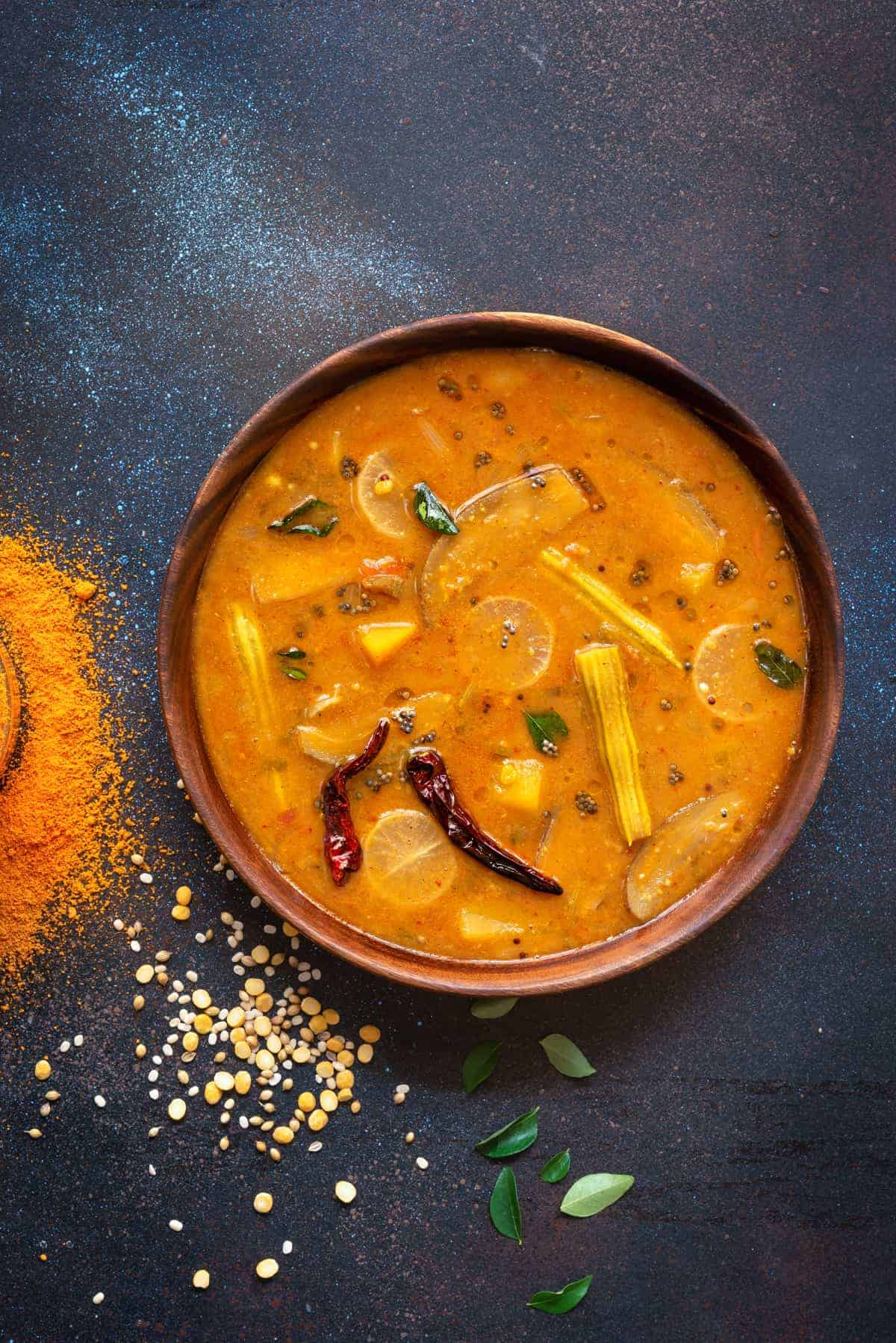 Vegetable Sambar dal in a wooden bowl, some sambar powder and spices spread around.