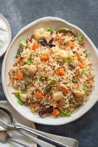 Close up shot of mix veg pulao or vegetable pulao on white ceramic plate.